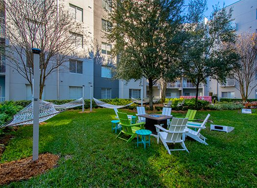 Bell Channelside apartments courtyard with hammocks firepit and corn hole